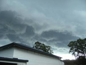 dark clouds rolling over a house and trees